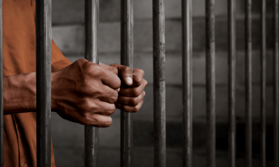 A man with acquired brain injury holding the bars of a cell. Close up on two hands holding the bars