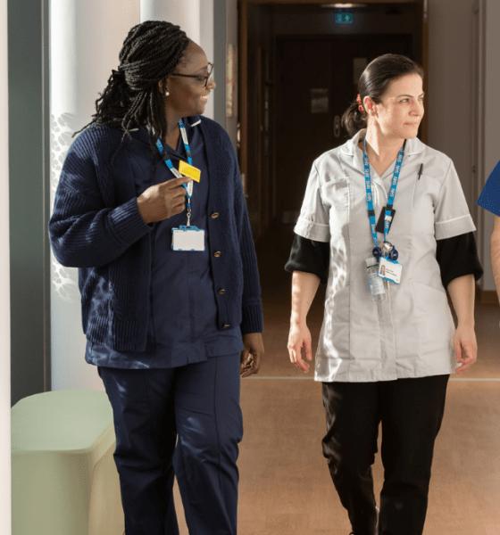 Three members of NHS staff walking down a corridoor in uniform using the Perfect Ward system