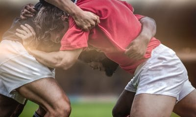 rugby players in a scrum with their heads and shoulders down