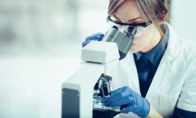 A doctor investigating multiple sclerosis (MS) research through a telescope