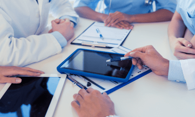 A new care platform: Doctors are sitting around in a circle at a table using tablets and notepads to discuss care management