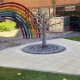 The NHS memory tree marking the death of colleagues stands on a white space with a big rainbow in the background