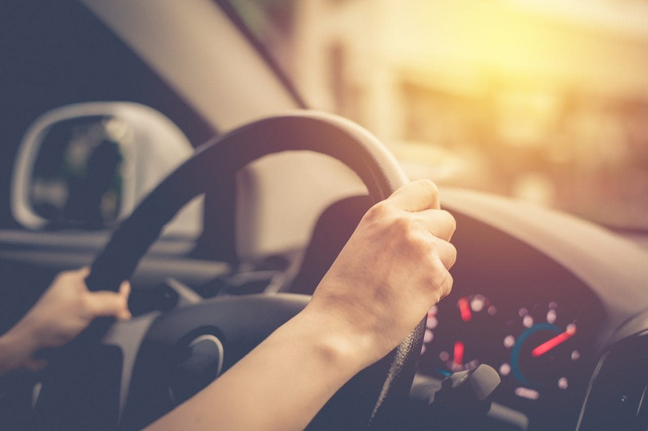 A person driving while holding the steering wheel with both hands