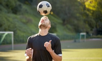 A professional footballer balances a football on his head marking the release of a study into footballers risk of dementia